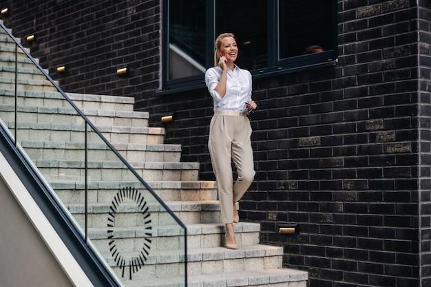 Glimlachende aantrekkelijke blonde modieuze dame die de trap afloopt en aan de telefoon spreekt