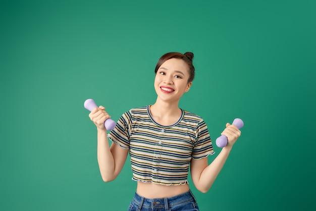 Glimlachende aantrekkelijke jonge aziatische vrouw die oefening met domoor oefent over groen.