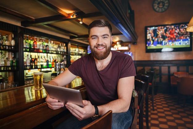 Glimlachende aantrekkelijke jonge man die tablet gebruikt en bier drinkt in de pub