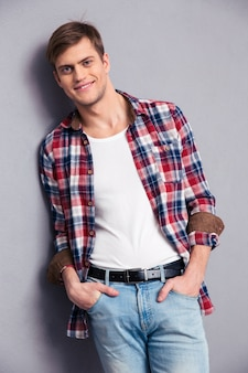 Glimlachende aantrekkelijke jonge man in geruit hemd en spijkerbroek poseren over grijze muur
