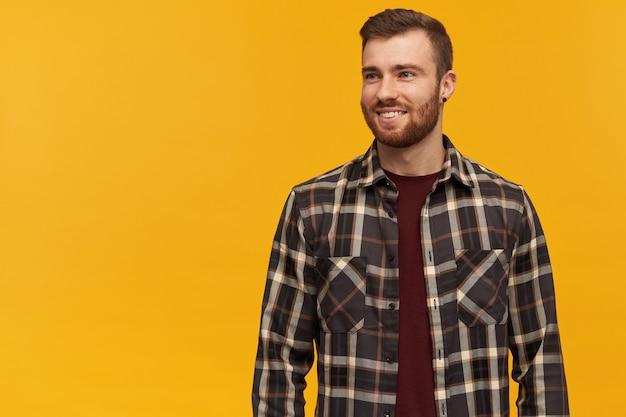 Glimlachende aantrekkelijke jonge man in geruit overhemd met baard die zich en weg naar de kant over gele muur bevinden kijken