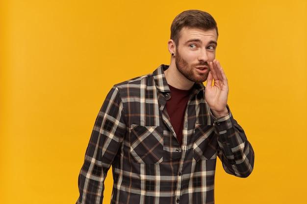 Glimlachende aantrekkelijke jonge man in geruit overhemd met baard houdt hand dichtbij gezicht en vertelt een geheim dat over gele muur wordt geïsoleerd