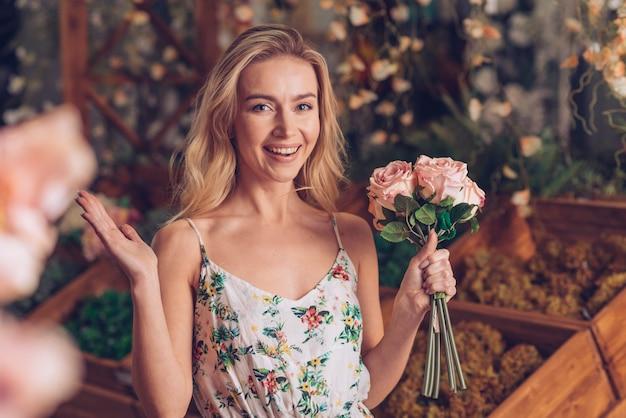 Glimlachende aantrekkelijke jonge vrouw die roze rozen in hand houdt