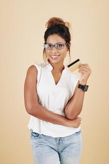 Glimlachende aantrekkelijke jonge vrouw in glazen met creditcard, geïsoleerd op beige background