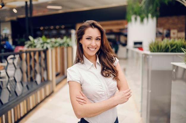 Glimlachende aantrekkelijke kaukasische vrouw die zich voor koffie met gekruiste wapens bevindt.