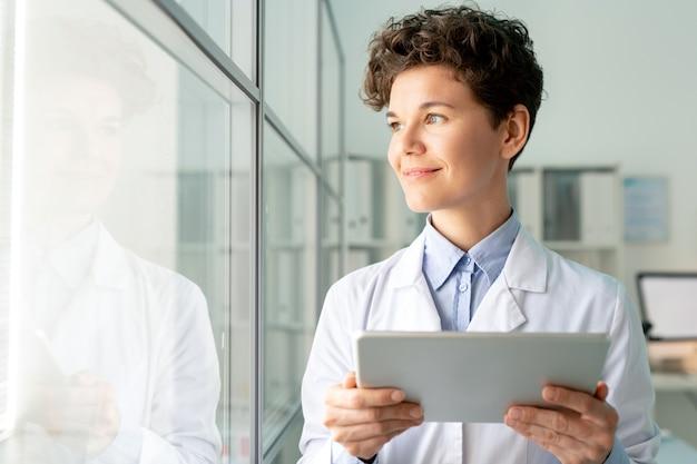 Glimlachende aantrekkelijke laboratoriummedewerker met krullend haar tevreden met onderzoeksresultaten met behulp van digitale tablet