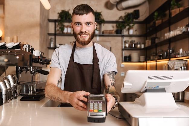Glimlachende aantrekkelijke man-barista die achter de toonbank in de coffeeshop staat en kaartlezerapparaat geeft
