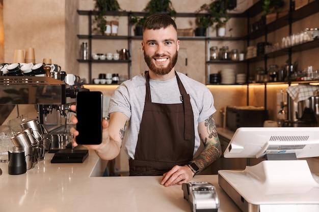 Glimlachende aantrekkelijke man barista staande achter de toonbank in de coffeeshop, met een leeg scherm mobiele telefoon