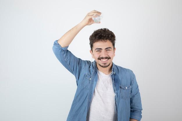 Glimlachende aantrekkelijke man die staat en een glazen pot vasthoudt.
