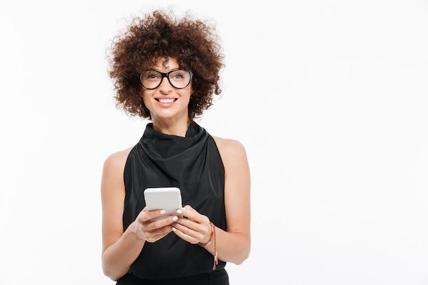 Glimlachende aantrekkelijke onderneemster die in oogglazen mobiele telefoon houdt
