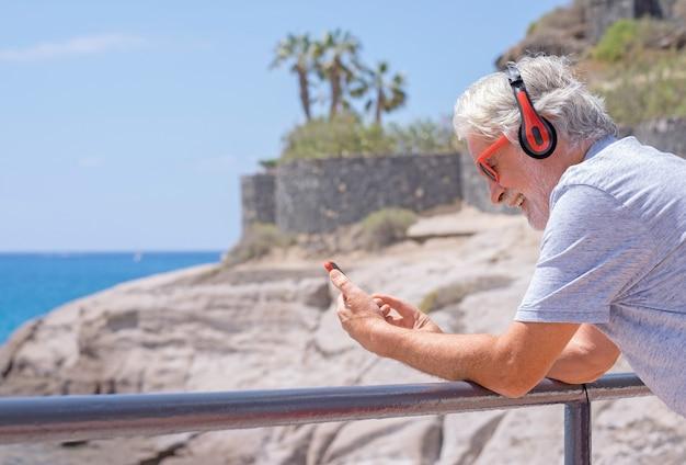 Glimlachende aantrekkelijke senior man met behulp van mobiele telefoon aan zee, met rode koptelefoon. gelukkig pensioen. horizon over het water