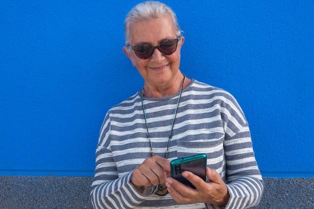 Glimlachende aantrekkelijke senior vrouw met wit haar met behulp van slimme telefoon app een bericht sturen naar vrienden - blauwe achtergrond - tech en sociale ouderen