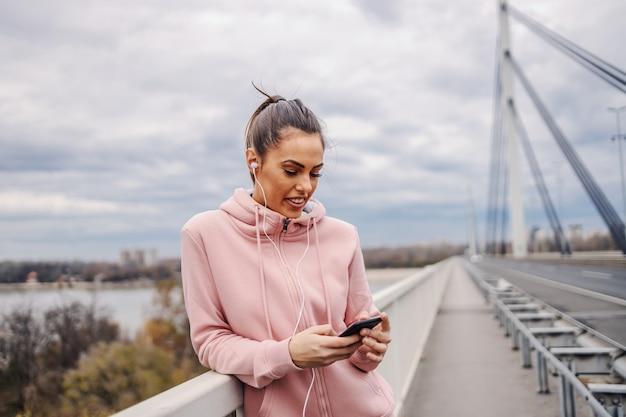Glimlachende aantrekkelijke sportvrouw die op brugleuning leunt, hoofdtelefoon in oren heeft en motiverende lied op slimme telefoon kiest alvorens te rennen. stedelijk leven concept.