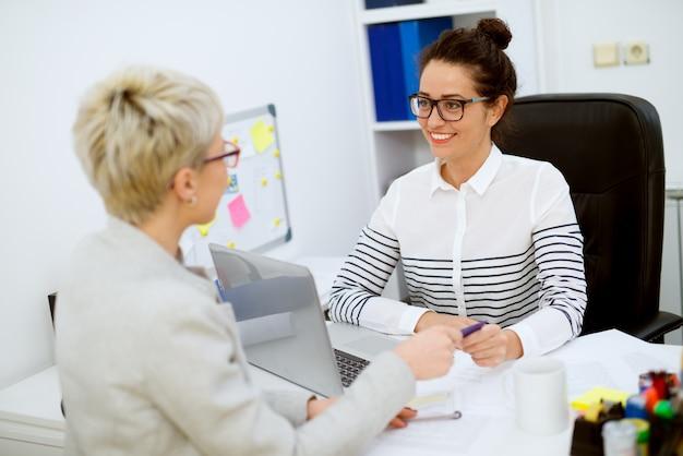 Glimlachende aantrekkelijke succesvolle financiële assistentvrouw van middelbare leeftijd met oogglazen die de vrouwklant zitten en een bankkaart nemen in het bureau.