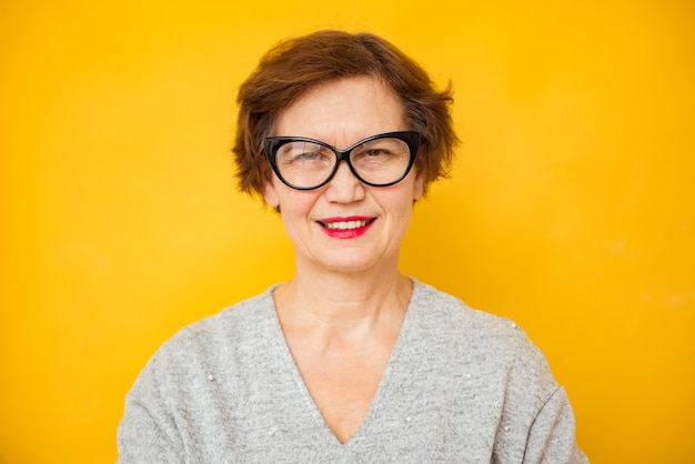 Glimlachende aantrekkelijke toevallige rijpe mooie vrouw van middelbare leeftijd die camera op gele achtergrond bekijkt