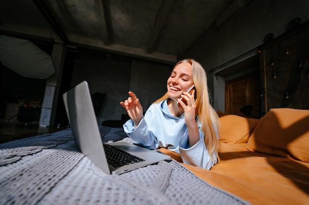 Glimlachende aantrekkelijke vrouw die op bed ligt dat door smartphone spreekt