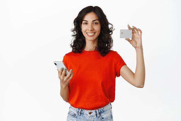Glimlachende aantrekkelijke vrouw die smartphone vasthoudt en creditcard toont, betaalt voor online bestelling, winkelt in mobiele app op wit