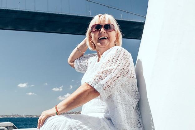 Glimlachende aantrekkelijke vrouw in zonnebril op het grote witte schip of jacht