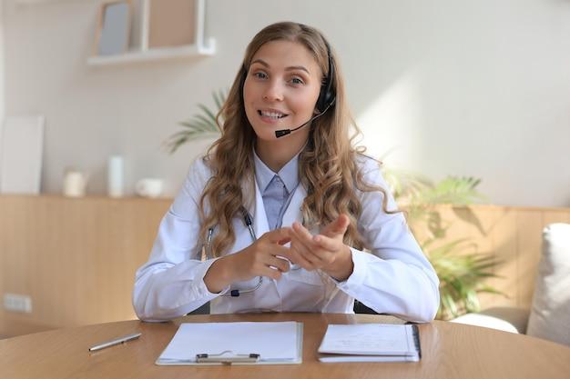 Glimlachende aantrekkelijke vrouwelijke arts praten op camera met patiënt.