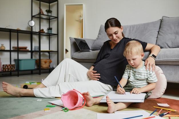 Glimlachende aantrekkelijke zwangere jonge moeder zittend op tapijt met verspreid speelgoed en omhelzende zoon die tekenen