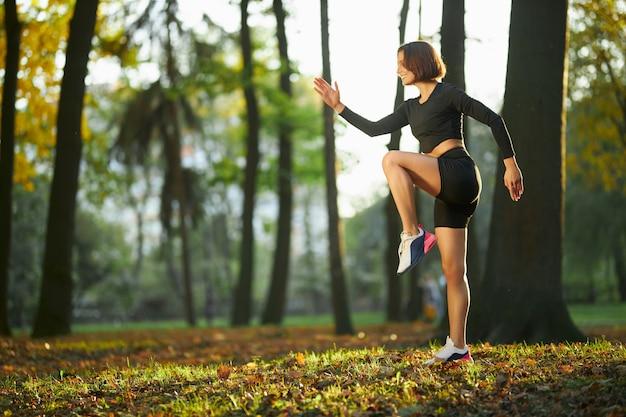 Glimlachende actieve vrouw die fitnessoefeningen doet bij park at