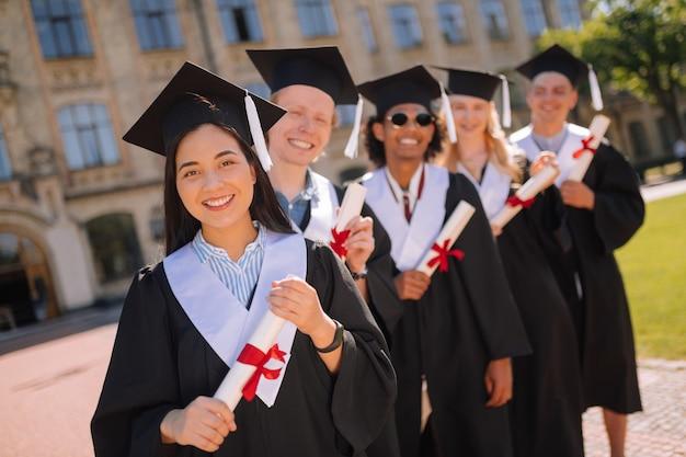 Glimlachende afgestudeerden met hun diploma's met rode linten erop
