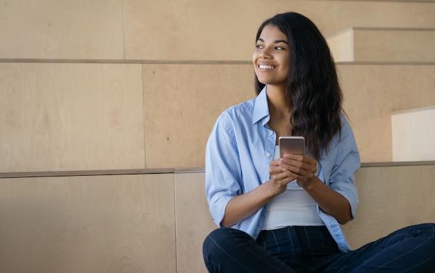 Glimlachende african american vrouw met behulp van mobiele telefoon wegkijken, werken vanuit huis