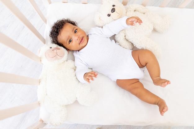 Glimlachende afrikaans-amerikaanse kleine baby in wit slaapbed met beerspeelgoed