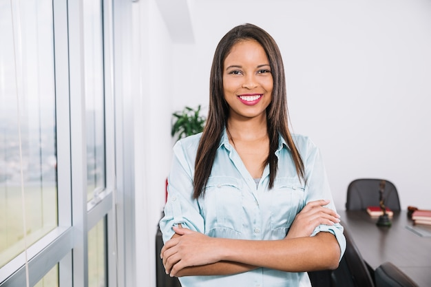 Glimlachende afrikaanse amerikaanse jonge dame dichtbij venster