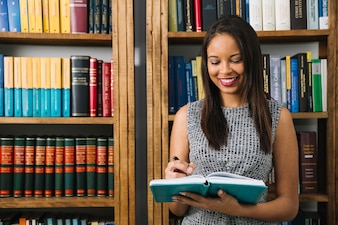 Glimlachende Afrikaanse Amerikaanse jonge dame met boek