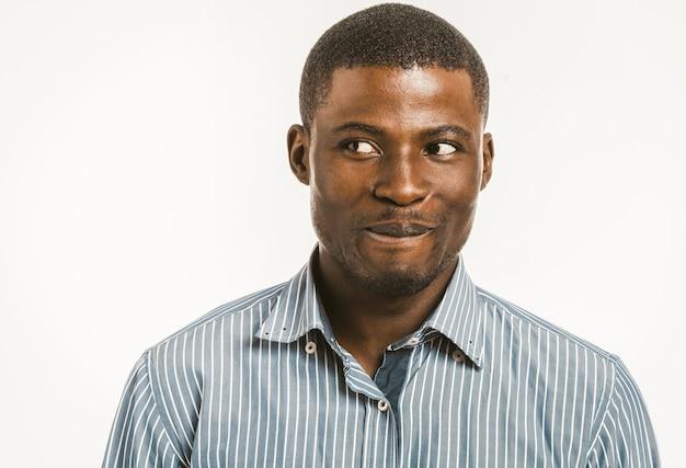 Glimlachende afrikaanse amerikaanse mens die kant bekijkt.