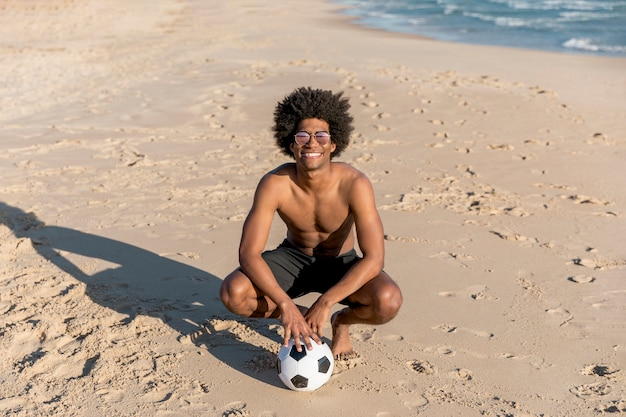 Glimlachende afrikaanse amerikaanse mensenzitting met bal op de zomerstrand