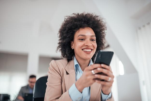 Glimlachende afrikaanse amerikaanse onderneemster die slimme telefoon in mede werkend bureau, lage hoekmening met behulp van.