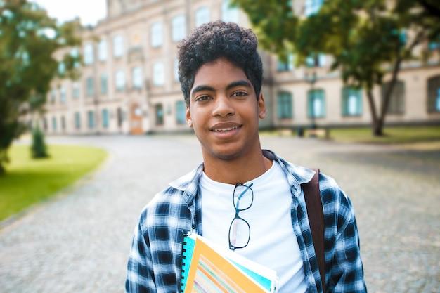 Glimlachende afrikaanse amerikaanse student met glazen en met boeken dichtbij universiteit. portret van een gelukkige zwarte jonge man die zich op een universiteit bevindt