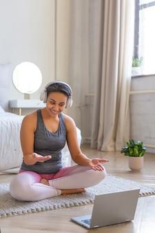 Glimlachende afrikaanse amerikaanse vrouw alvorens online te trainen. ze praat met de coach terwijl ze de training bespreekt. verticale foto.