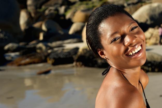 Glimlachende afrikaanse amerikaanse vrouw bij het strand