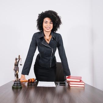 Glimlachende afrikaanse amerikaanse vrouw dichtbij lijst met smartphone, boeken, document en standbeeld