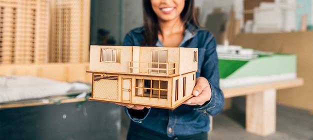 Glimlachende afrikaanse amerikaanse vrouw die model van huis toont
