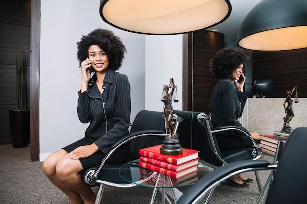 Glimlachende afrikaanse amerikaanse vrouw die op smartphone op leunstoel in bureau spreken
