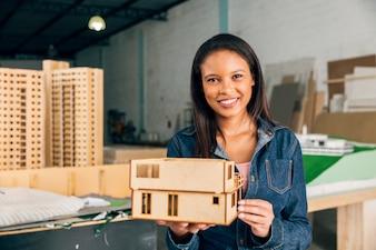 Glimlachende Afrikaanse Amerikaanse vrouw met model van huis