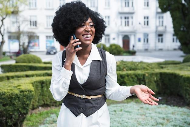 Glimlachende afrikaanse jonge onderneemster die op mobiele telefoon spreekt