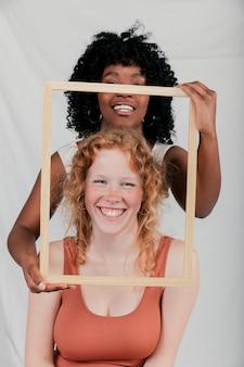 Glimlachende afrikaanse jonge vrouw die houten frame voor kaukasisch wijfje houdt
