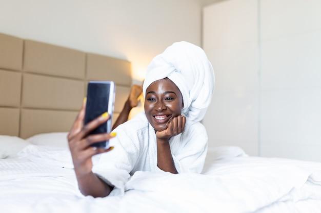 Glimlachende afrikaanse jonge vrouw die op bed in badjas met haar mobiele telefoon ligt die een selfie neemt.