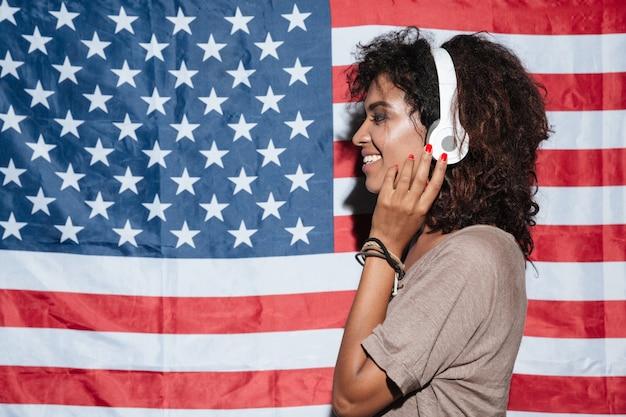 Glimlachende afrikaanse jonge vrouw die zich over de vlag van de vs het luisteren muziek bevindt