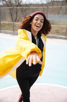 Glimlachende afrikaanse krullende jonge dame die gele laag draagt