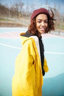 Glimlachende afrikaanse krullende jonge vrouw die gele laag draagt