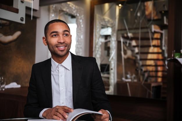 Glimlachende afrikaanse man in pak met dagboek in hotel