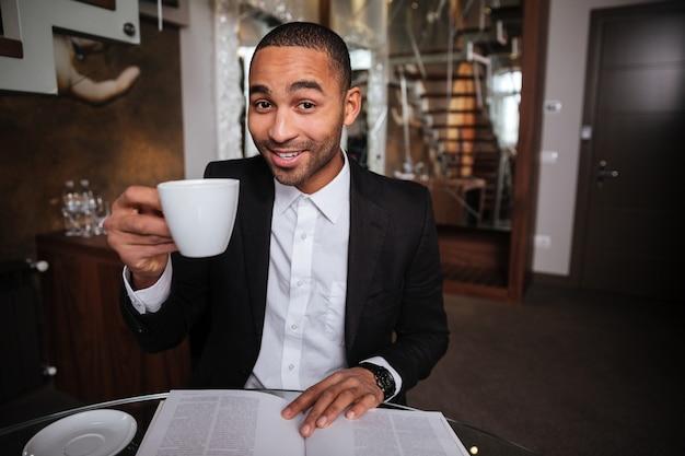 Glimlachende afrikaanse man in pak zit met dagboek en koffie in hotel