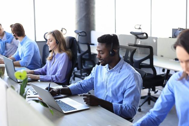 Glimlachende afrikaanse mannelijke callcenter-operator met koptelefoon zittend op modern kantoor met collega's op de backgroung, online raadplegen.