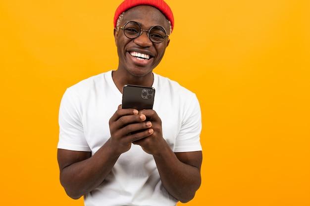 Glimlachende afrikaanse mens die een smartphone in zijn handen houdt en een bericht op een gele achtergrond verzendt